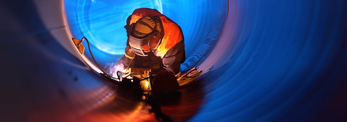 A man welding within a tube